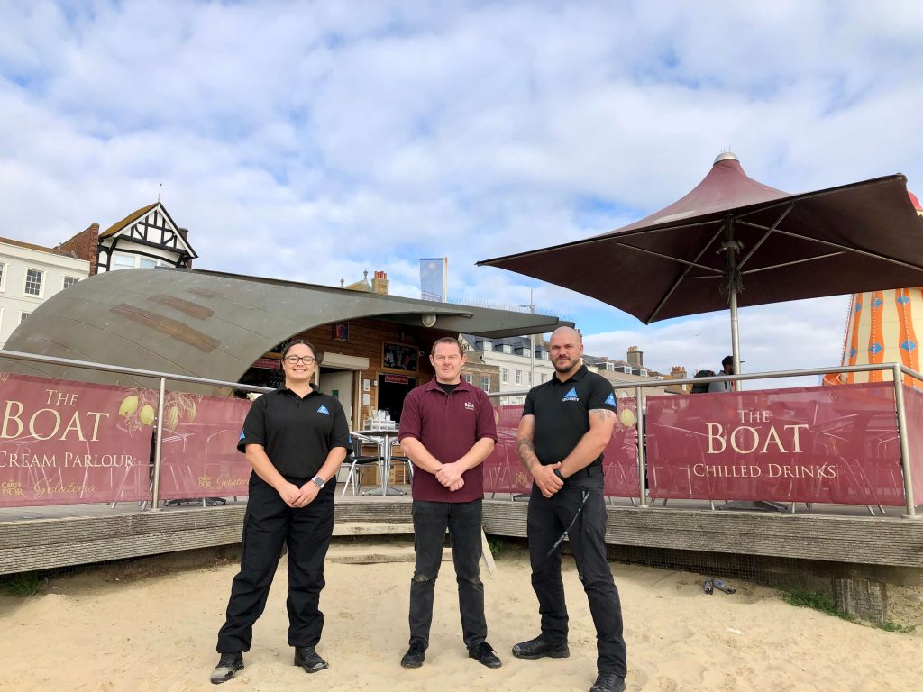 The Real World Services Team with Darren Deadman part of Weymouths Beachside community, in front of The Boat Cafe on Weymouth beach.